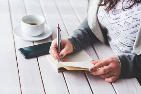 A woman writing her journal with a cup of coffee.