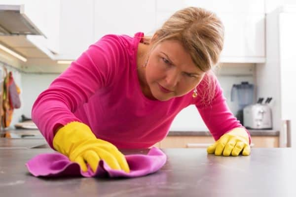 A woman cleaning table obsessively.